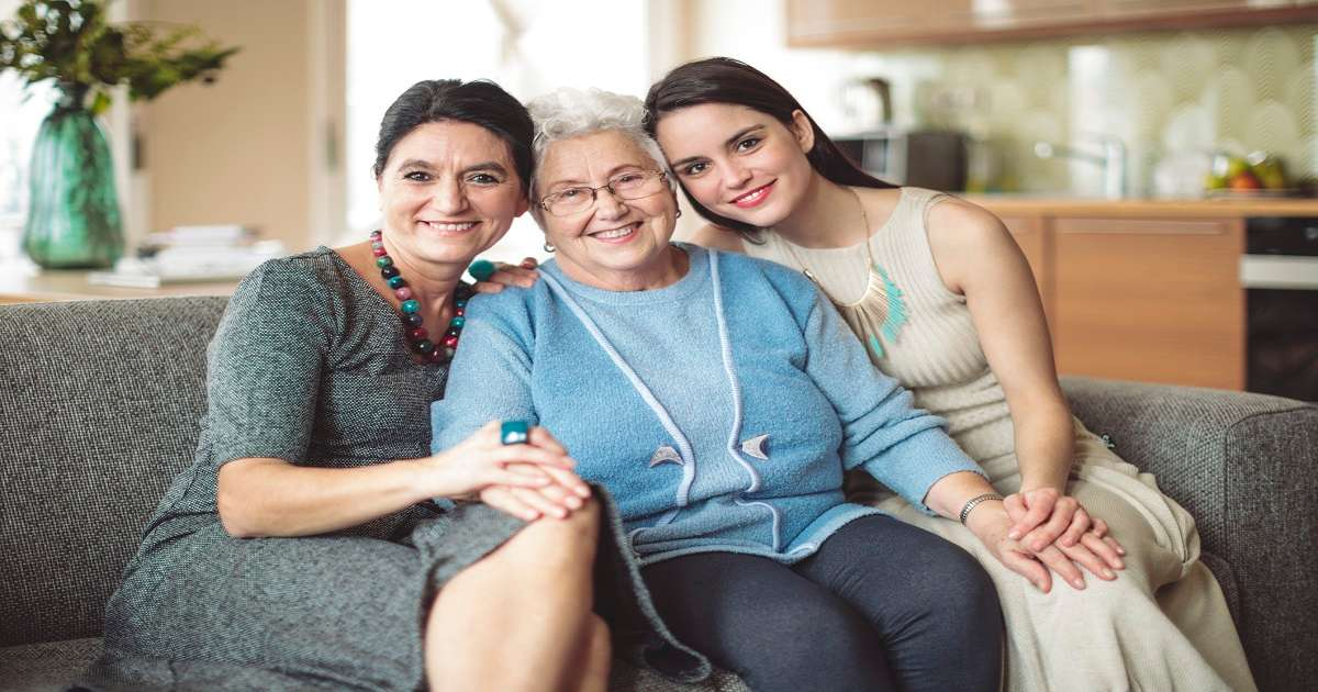Grandmother, mother and daughter sitting together at home.
