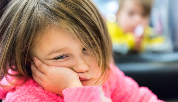 Young girl having difficulty staying awake at school.