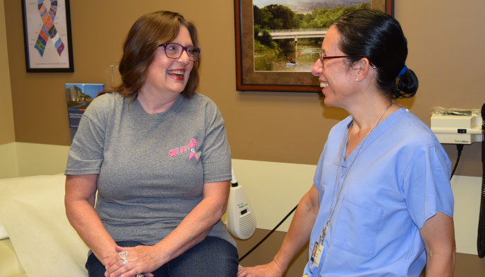 Breast cancer survivor, Alicia Porter, and Dr. Laura Miegge smiling in patient room