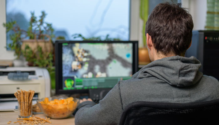Male playing video games on computer with snacks lying on table. Is he addicted to gaming?