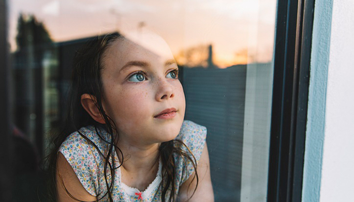young girl looking out the window; Coronavirus Symptoms in Kids: What is PMIS?
