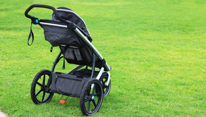 Black running stroller on grass, best baby products for active parents