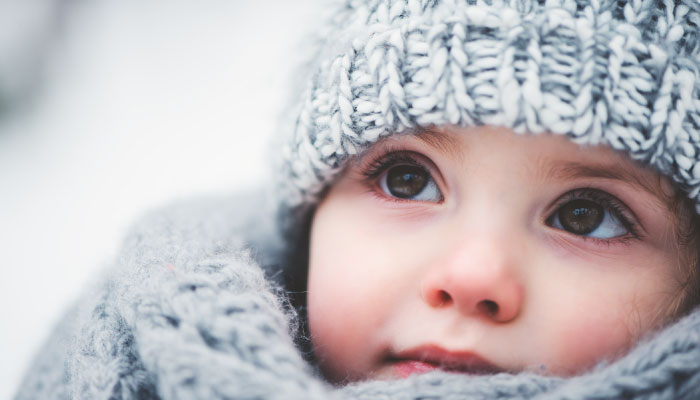 child with big brown eyes with a cozy hat and scarf