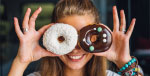 Woman holding two donuts up to her eyes, looking through the holes