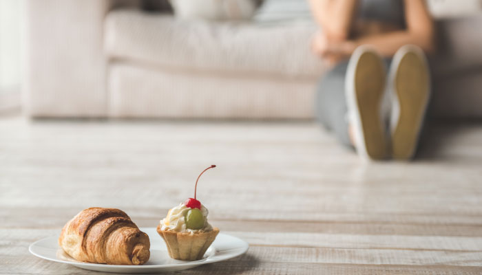Pastries on living room floor in front of woman struggling with disordered eating