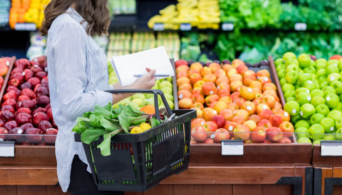 Woman gathering items on her healthy grocery list.