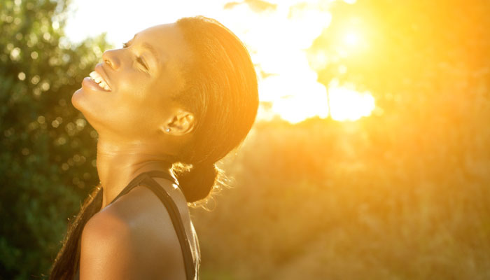 Woman smiles while enjoying the positive effects of the sun