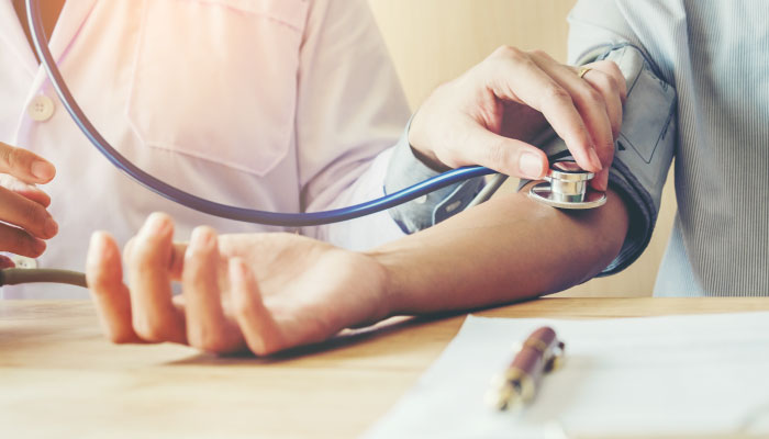 Doctor measuring adult blood pressure with new guidelines