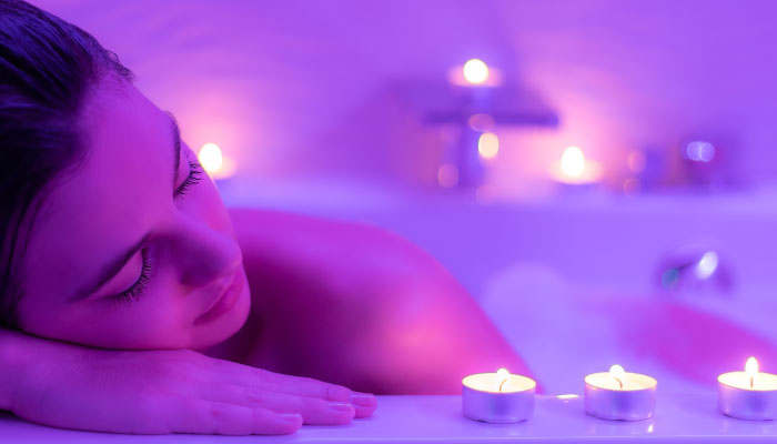 Woman in bathtub, relaxing with candles around the tub.