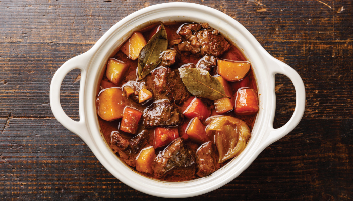 Picture of beef stew with vegetables on brown, wooden table.