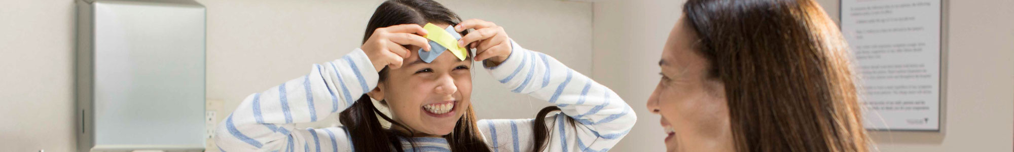 little girl is holding a band aid to her forehead